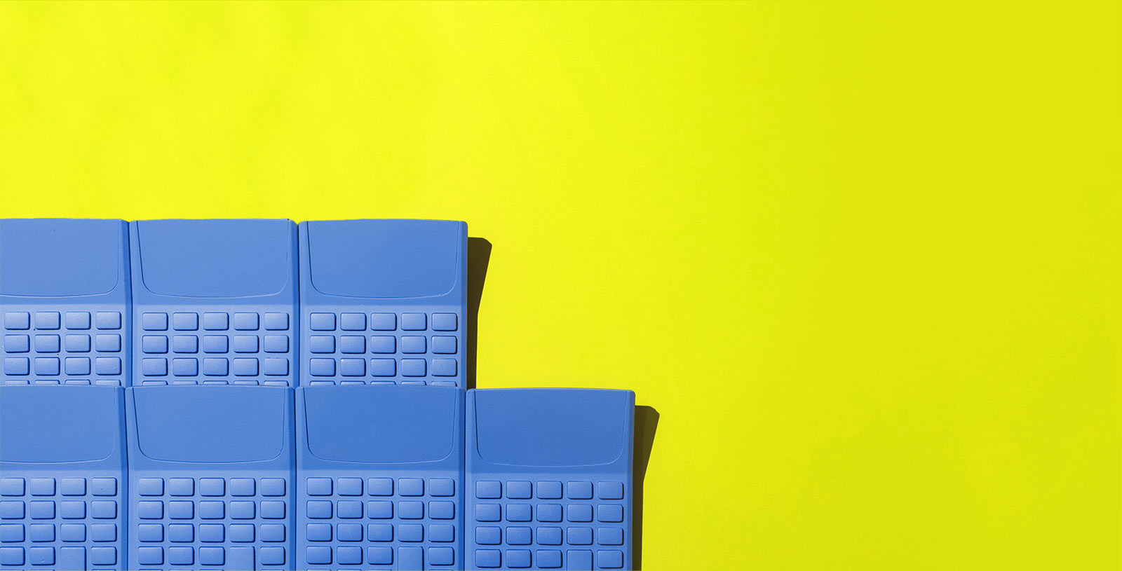 a group of blue calculators on a yellow background