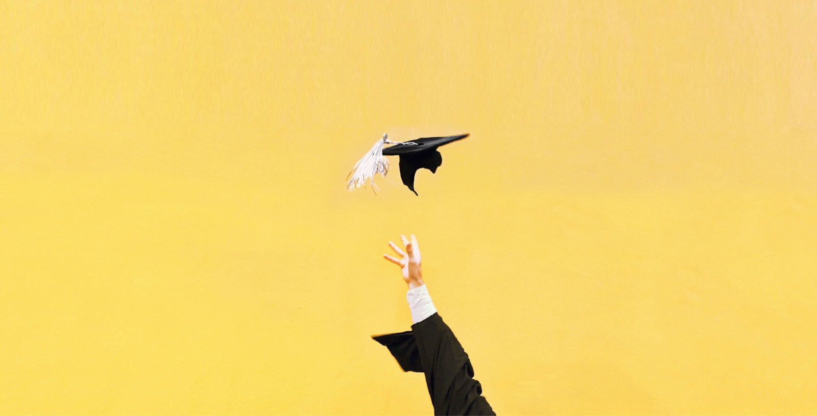 a hand grabbing for a student cap