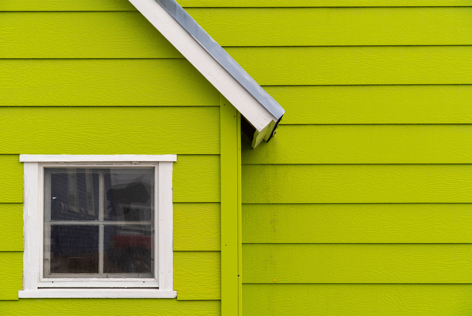 Bright green house with square window reflecting fixer upper topic