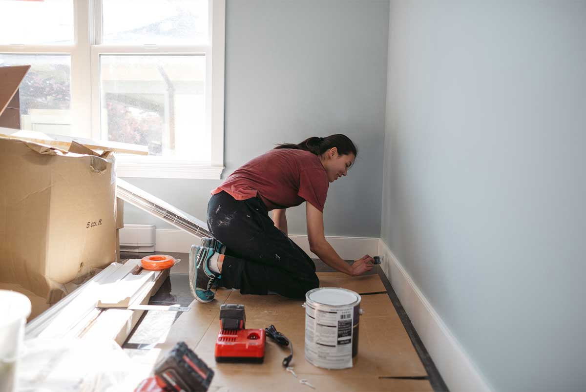 Woman painting baseboards white ina room that is being renovated