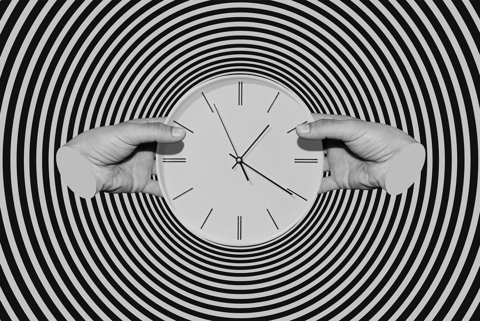hypnotic black and white image of two hands holding a clock