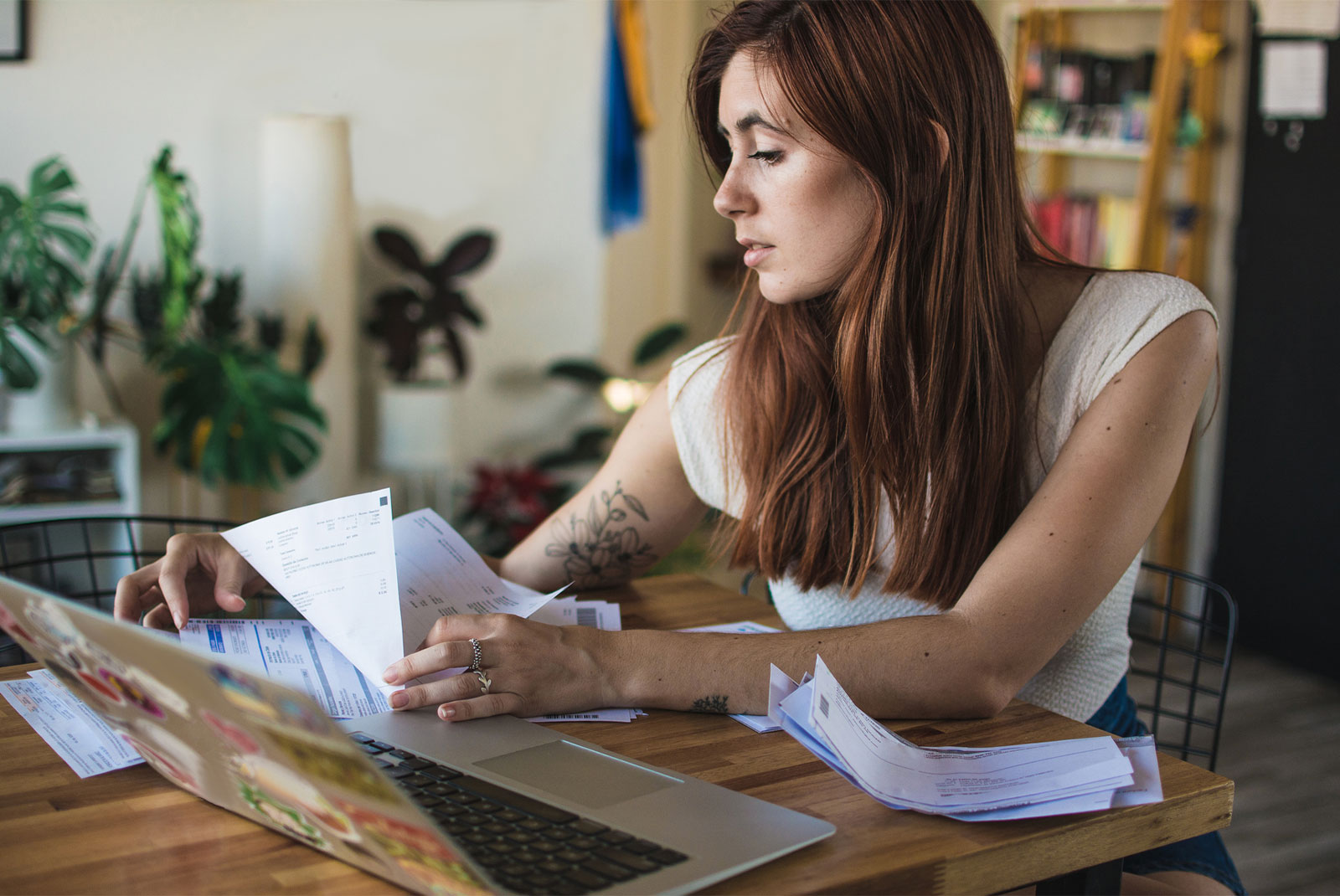 woman choosing a mortgage lender looking through papers and sitting at table