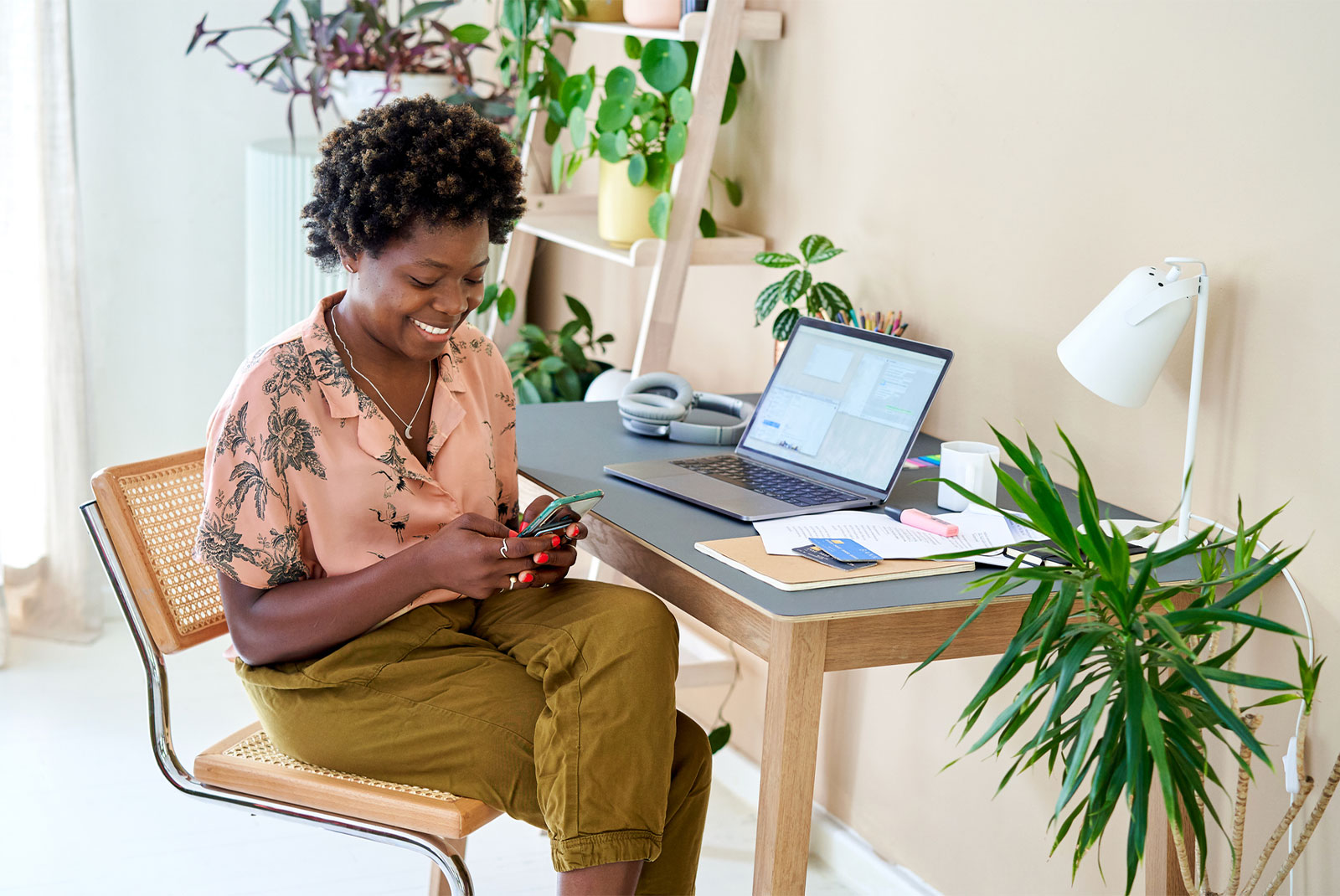woman checking her phone for the best refinance rates rates with computer nearby