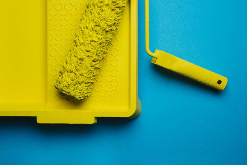 Yellow paint roller in a yellow paint tray