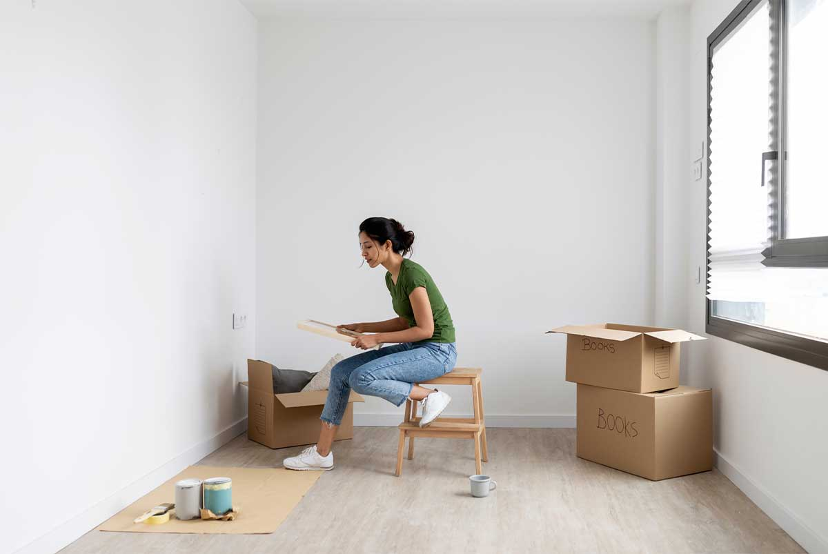 A young woman unpacking moving boxes in her new home