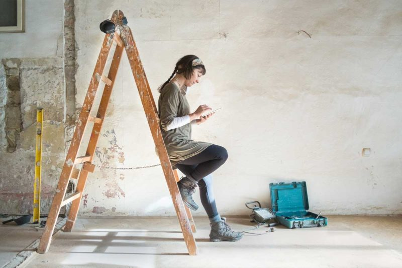 woman on phone leaning up against a ladder