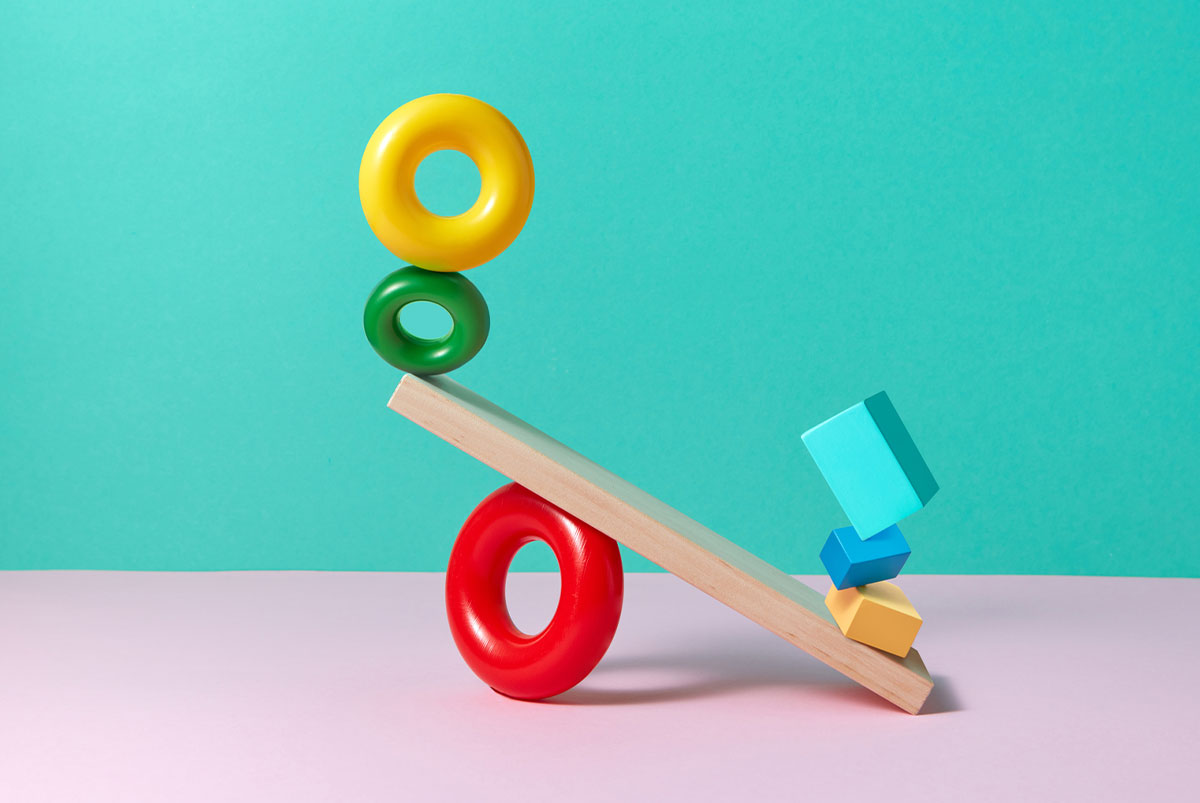 A pink and blue background with a plank balancing several colorful shapes