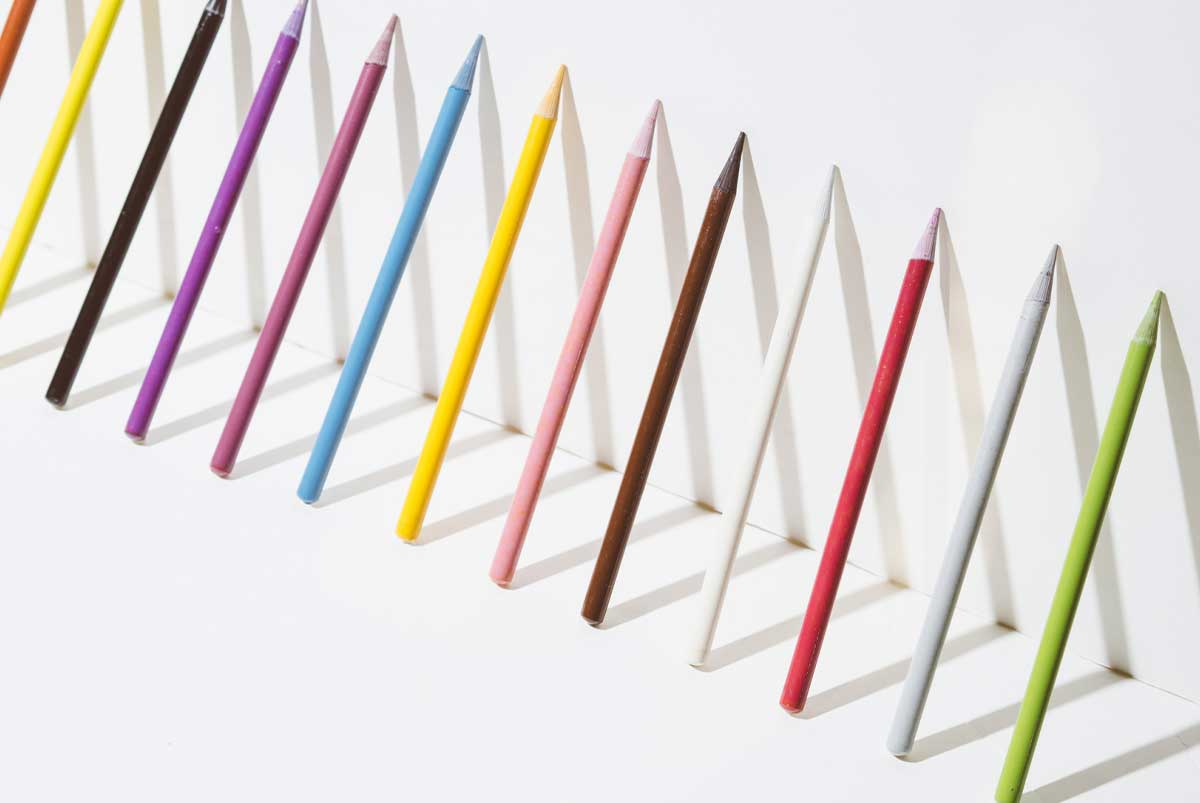 A row of colorful pencils leaning up against a white wall