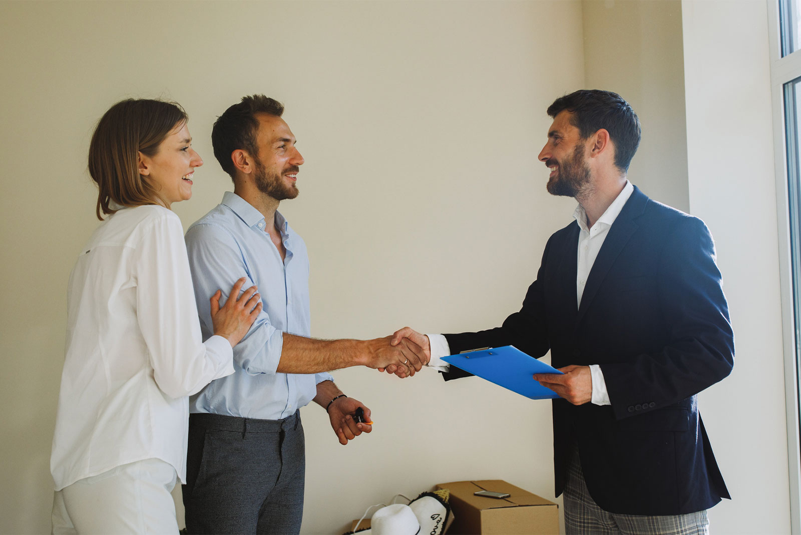 happy couple shaking hand with realtor who has blue folder