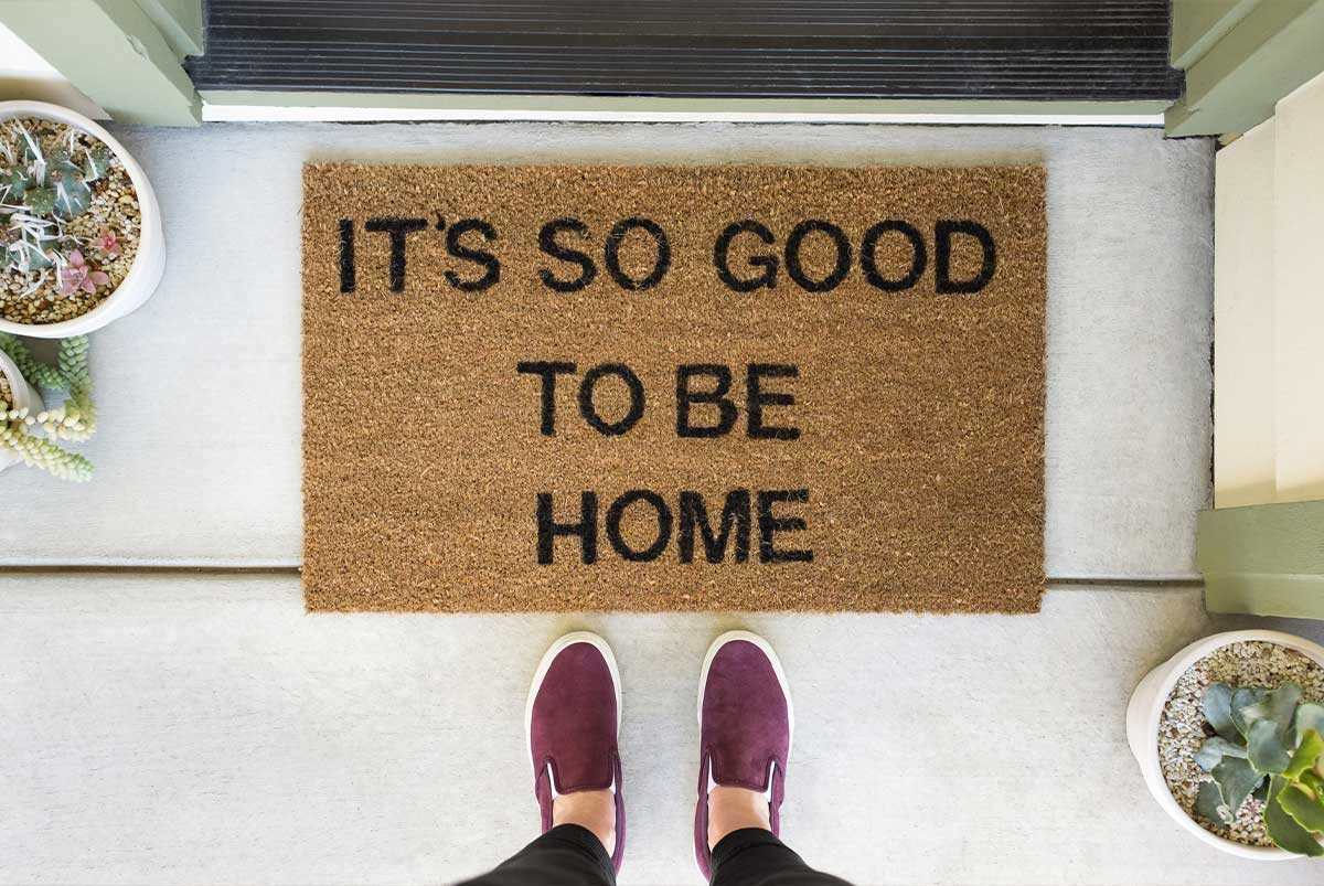 """A downward view of a doormat that says, """"It's so good to be home"""""""