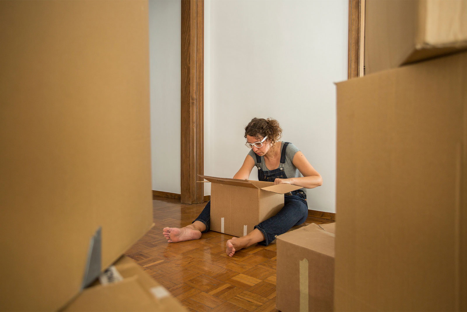 lady in dungarees looking inside a box for help as a first time homebuyer