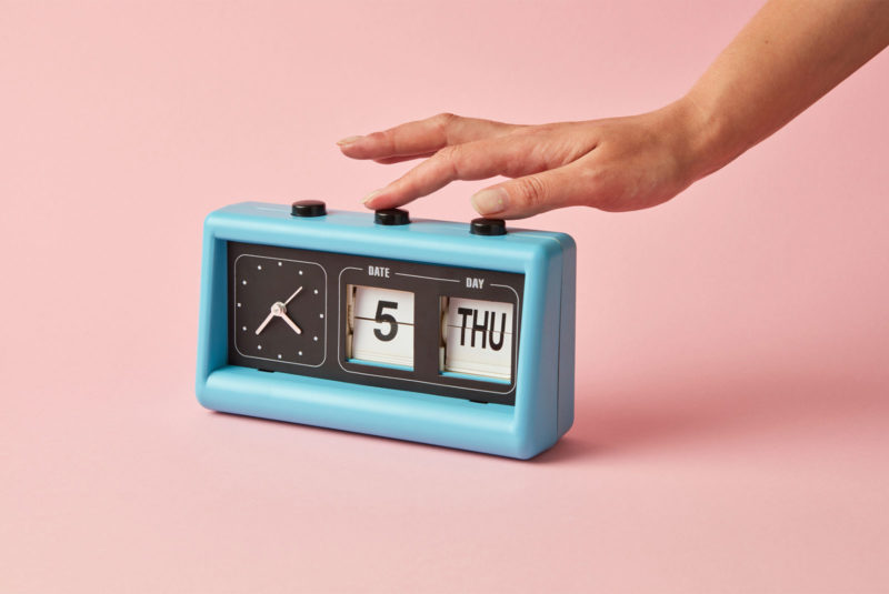someone setting a blue alarm clock thinking when is the best time to sell a house
